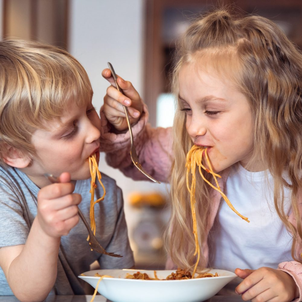 Cute children having fun while eating spaghetti with bolognese sauce at home